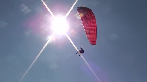 Parachute sliding with two people waving hands, passing the sun