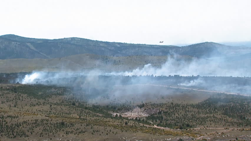 An aircraft extinguishing fire. Aerial helicopter shot.
