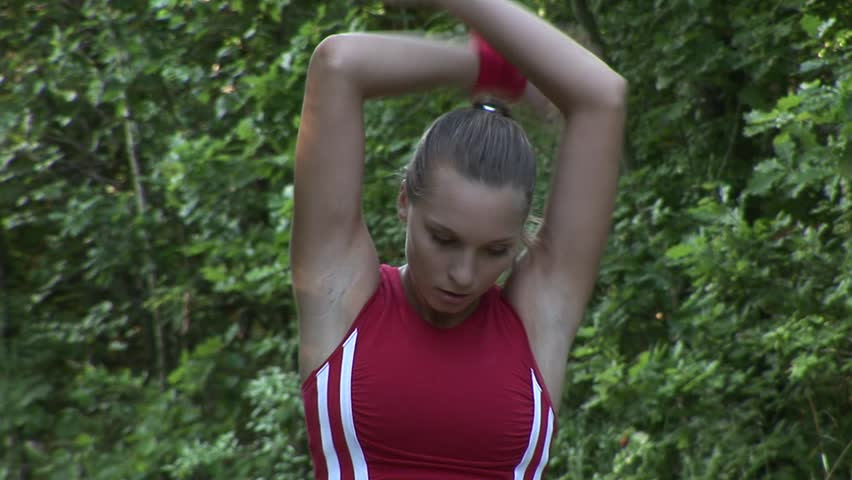 HD1080p Young attractive athletic woman stretching her arms in the black forest.