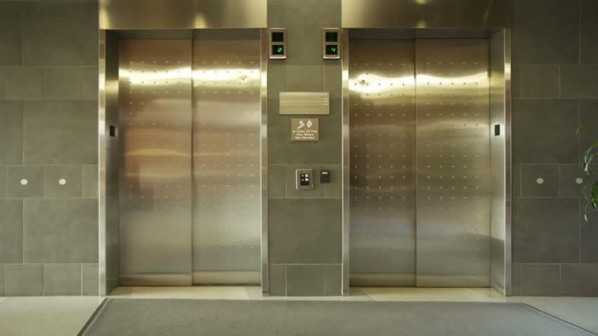 elevator. empty elevator arrives, doors open and close. wide, locked off shot.