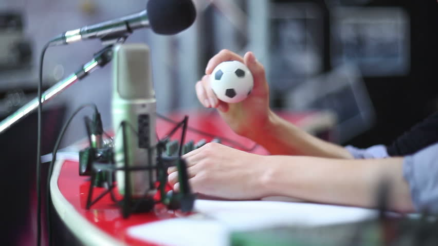 Man behind microphone taps toy ball and talks. Radio show dj on air