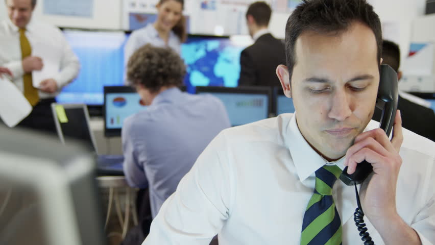 Young and ambitious stock market trader is doing a deal over the phone in a busy office filled with computers. The rest of his team are hard at work in the background. In slow motion. | Shutterstock HD Video #3672491
