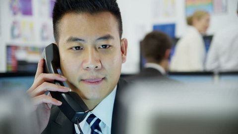 Young and ambitious stock market trader is doing a deal over the phone in a busy office filled with computers. The rest of his team are hard at work in the background.