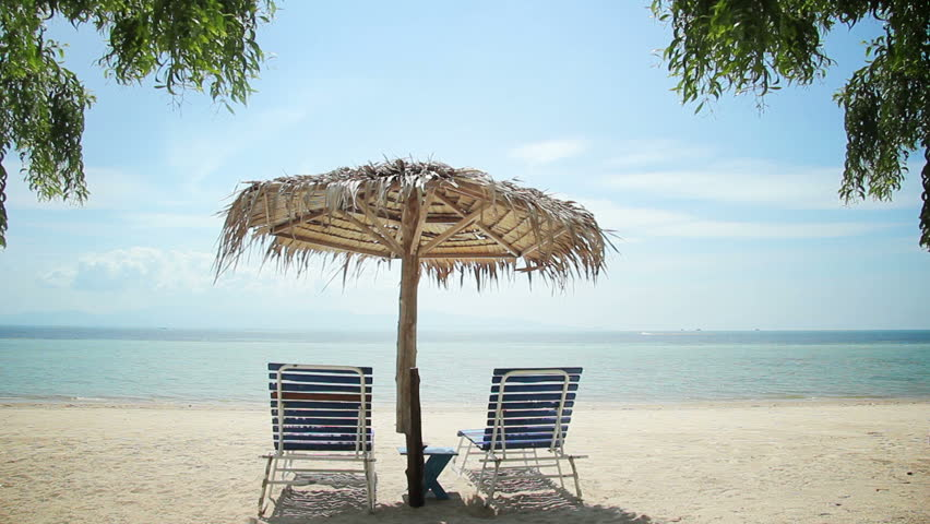 Vacation spot for couples - Beautiful tropical empty beach scene with two chairs under an umbrella, perfect for lovers & couples or romantic getaway video backgrounds