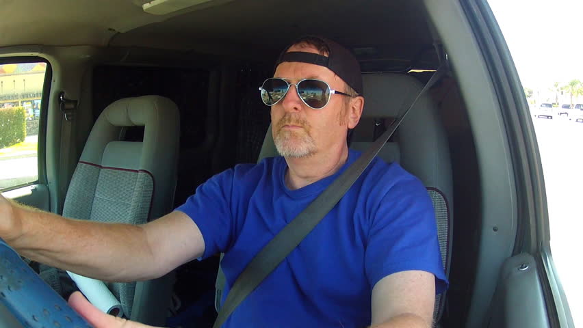 A medium shot of a middle aged man driving a delivery van on the streets of Los