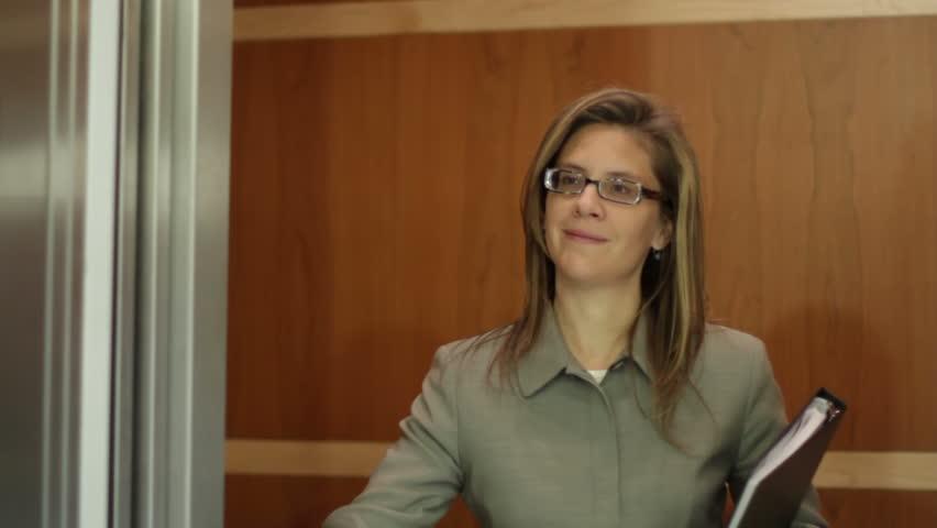 Business woman in elevator as doors close. Medium shot.