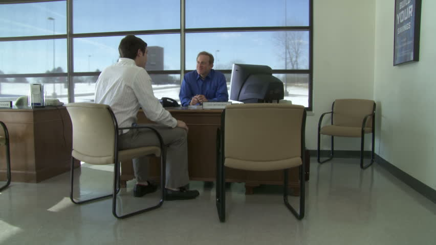 Customer discusses business with bank employee at a desk. Camera moves to follow
