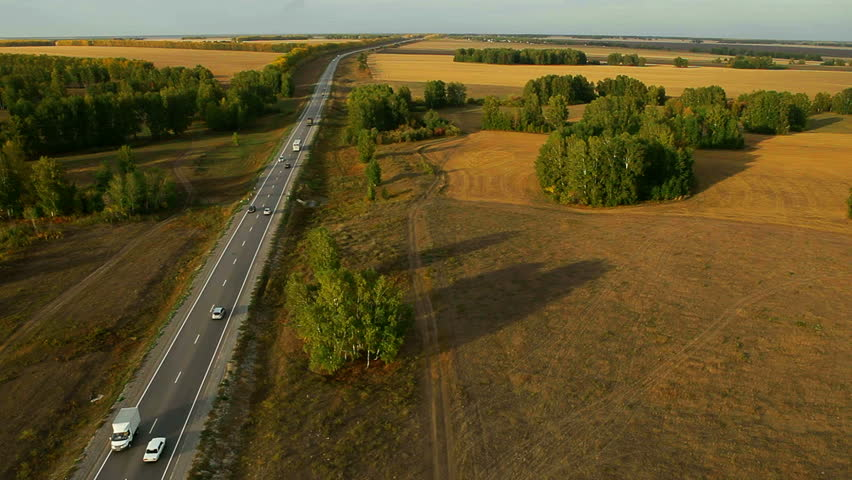 Aerial View. Flying over the road, field and beautiful autumn trees. Aerial camera shot. Landscape panorama.  Altai, Siberia.