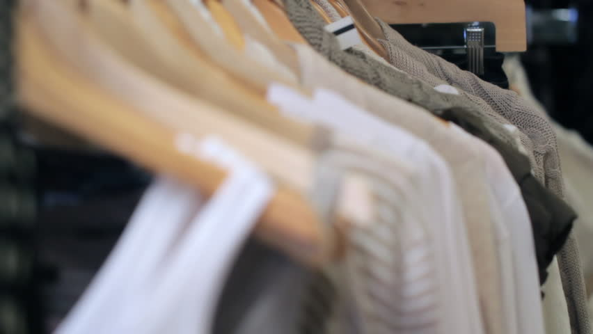 Woman's hands run across a rack of clothes and pick out something the shopper