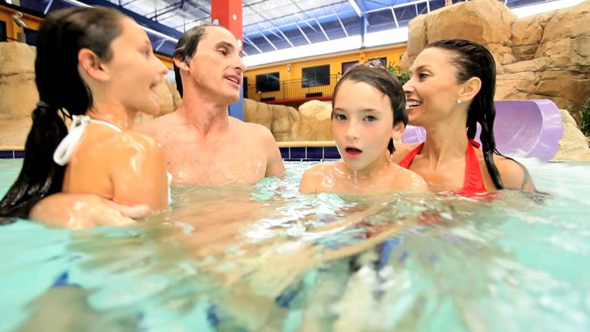 Close up happy Caucasian family underwater enjoying swimming pool at water theme park