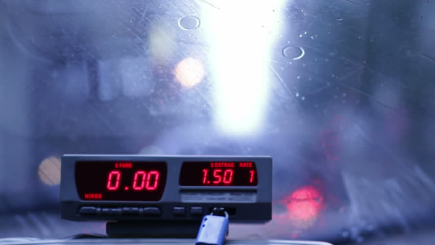 Taxi meter runs up a $100 fare on a very short trip. Rainy streets visible