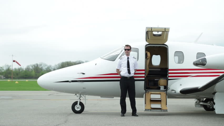 Female business executive walks up to private jet and is greeted by the pilot