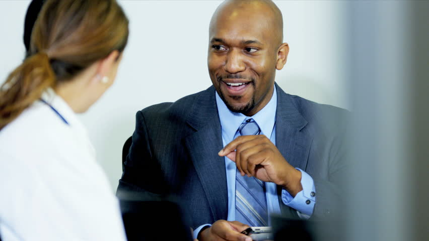 team multi ethnic medical executives being given advice by african american financial consultant shot on red epic stock footage video 3764321 shutterstock - Epic Consultant
