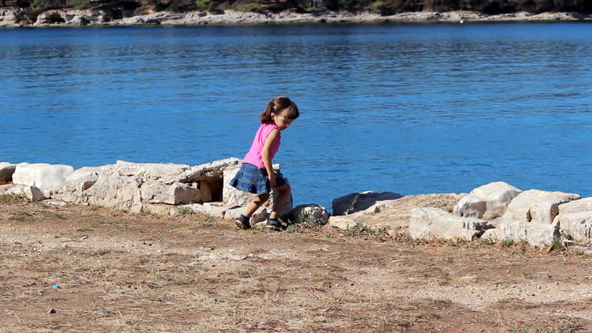 Kid and pebbles -  Small girl throwing pebbles at the sea.