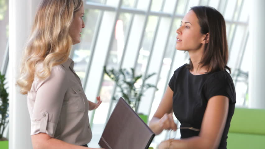 Two businesswoman in modern office discussing report together before they shake hands. Shot on Canon 5d Mk2 with a frame rate of 30fps   Shutterstock HD Video #3782297