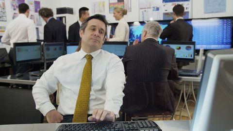 A very bored and tired mature businessman is struggling to stay awake at his desk while he is at work. As he lapses into sleep he looks around to check that his colleagues haven't noticed.