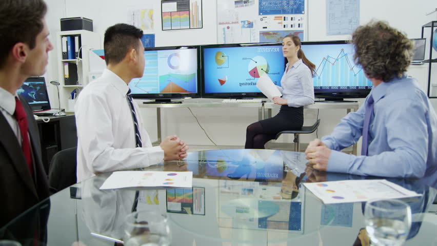 A beautiful businesswoman is giving a presentation in a room with lots of computer screens. Her colleagues listen to her ideas to encourage business growth and development. In slow motion.