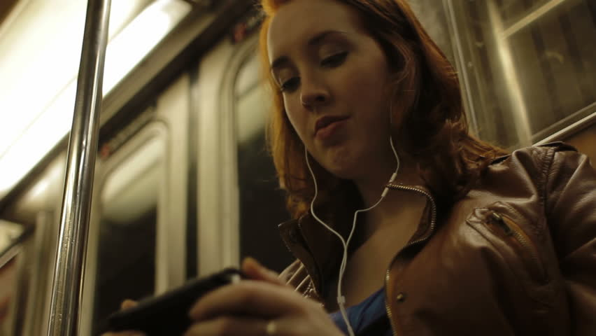 A woman watches a film on her smart phone whilst traveling on the New York subway
