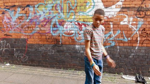 Street Dance - Mixed race boy street dancing in urban setting