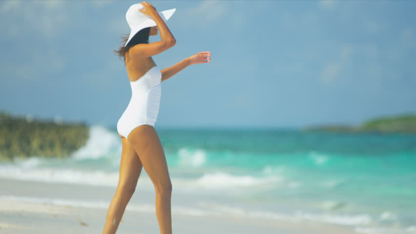 Pretty girl in swimsuit reveling being alone by ocean on remote island beach shot on RED EPIC