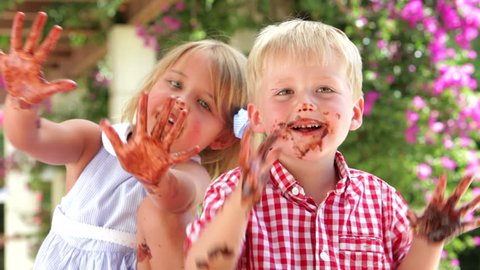 Children sitting at table waving chocolate covered hands to camera. Shot on Canon 5d Mk2 with a frame rate of 30fps
