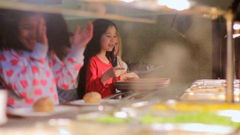 School food - children in a line receiving food from the school canteen
