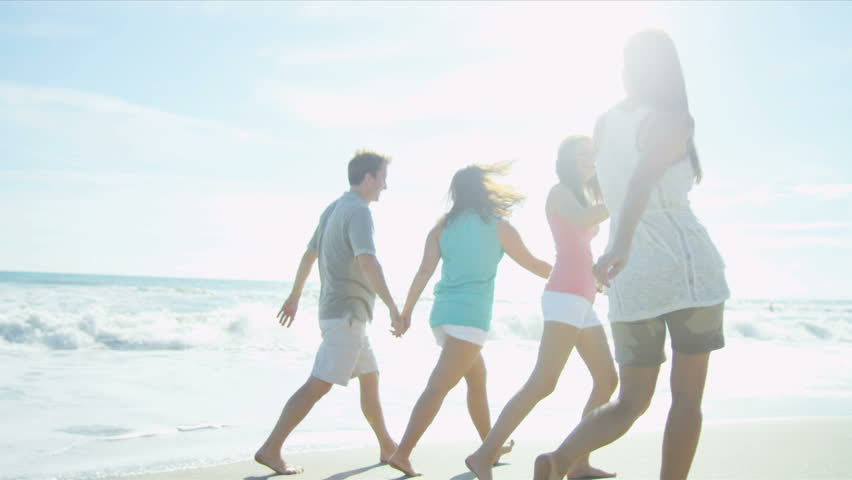 Healthy young family enjoying time together walking outdoors on the beach sun lens flare shot on RED EPIC