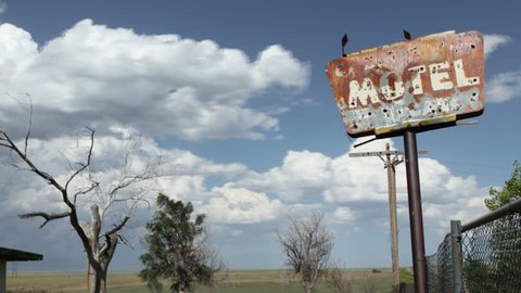 Timelapse of clouds behind an old, creepy motel sign, complete with bullet-holes, and old tree. HD 1080p Time lapse.