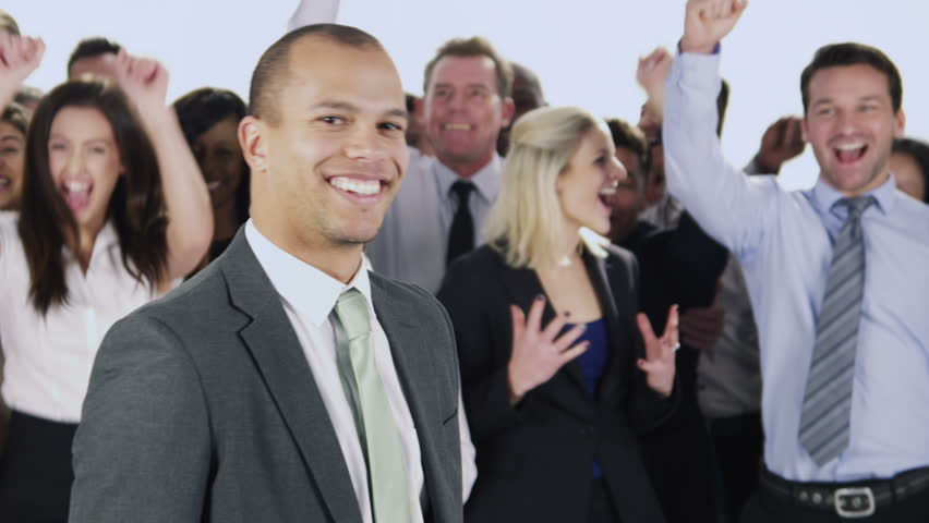 Portrait of a happy and diverse group of business people standing together isolated on white in a studio shot. One man smiles to the camera as the rest of his team jump and cheer. In slow motion.