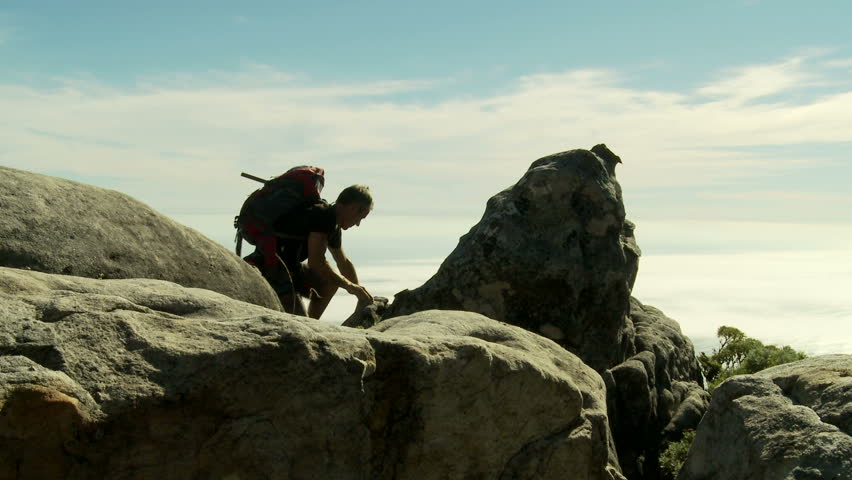 A rock climber wearing a backpack reaches the top of Table Mountain, South Africa, and takes in the misty view over the Atlantic Ocean