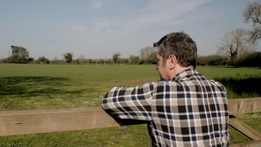 Farmer looking over field, CU