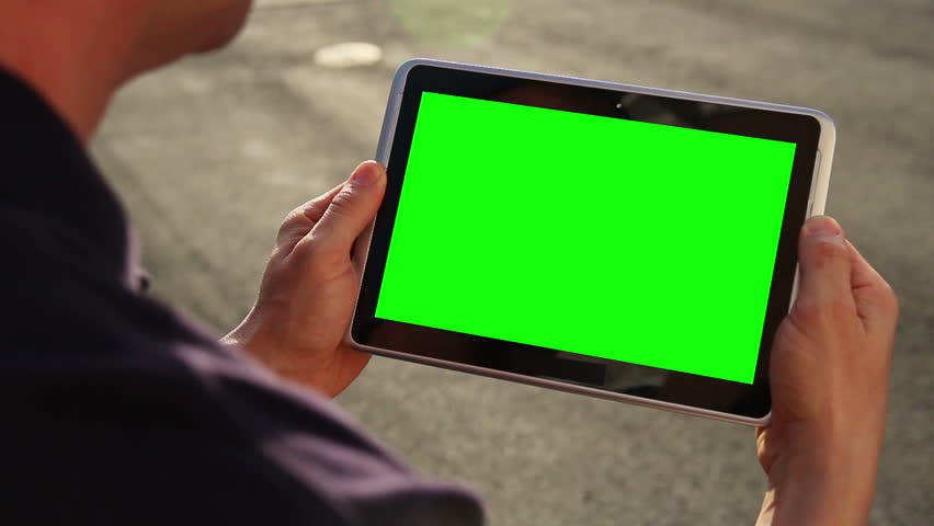 A man holds a blank tablet PC with a green screen for your own custom content. | Shutterstock HD Video #3833249
