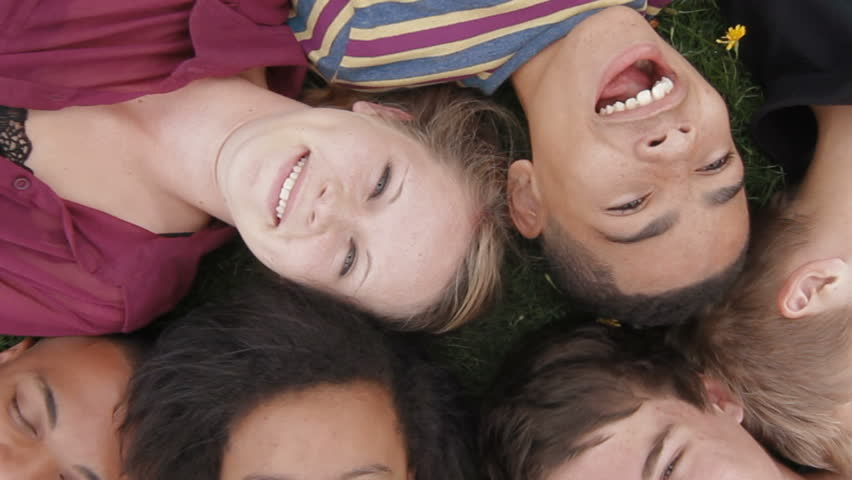 Teens lying on grass - A diverse group of teenagers lying on the grass looking up towards the camera