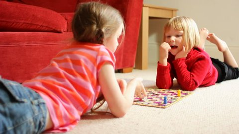 Two little girls playing a board game - the younger one wins!