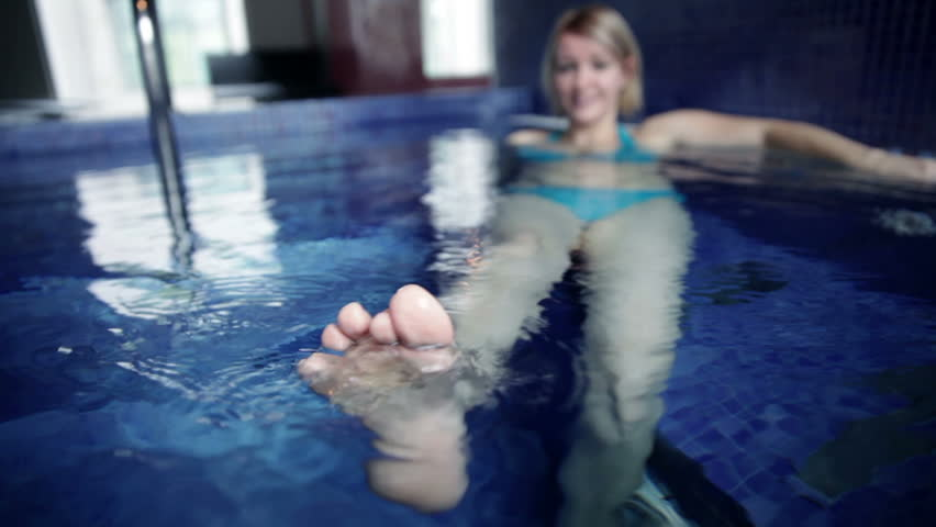 Close up shot of a waving foot and pretty young woman in blue bikini in the pool in the background