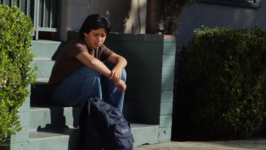 A teenage boy sits on some steps.  He looks around and seems to be frustrated or annoyed about something.