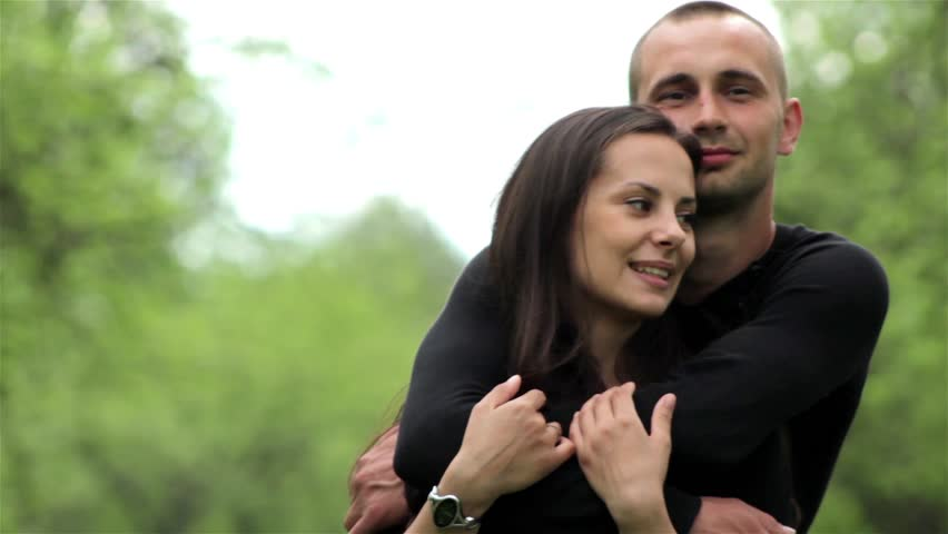 Portrait of a white European couples in love. Couple in love cuddling in a park.Happy joyful couple.