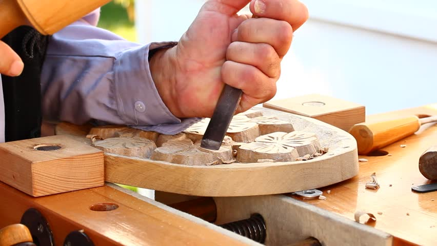 Work of artist, male hands carving wood