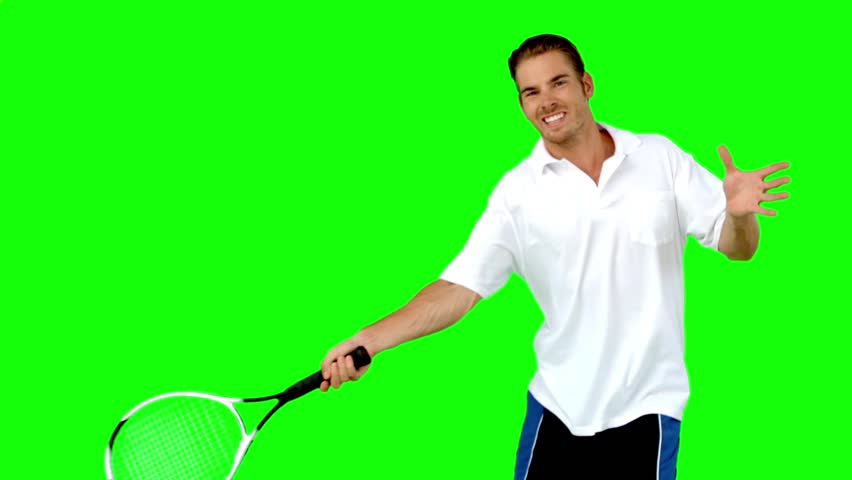 Young man playing tennis in slow motion on green screen