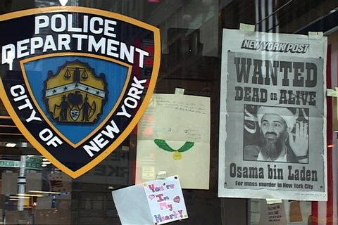 NEW YORK CITY - SEPTEMBER 29, 2001: NYPD seal and Osama bin Laden wanted poster displayed in window of Times Square police station.