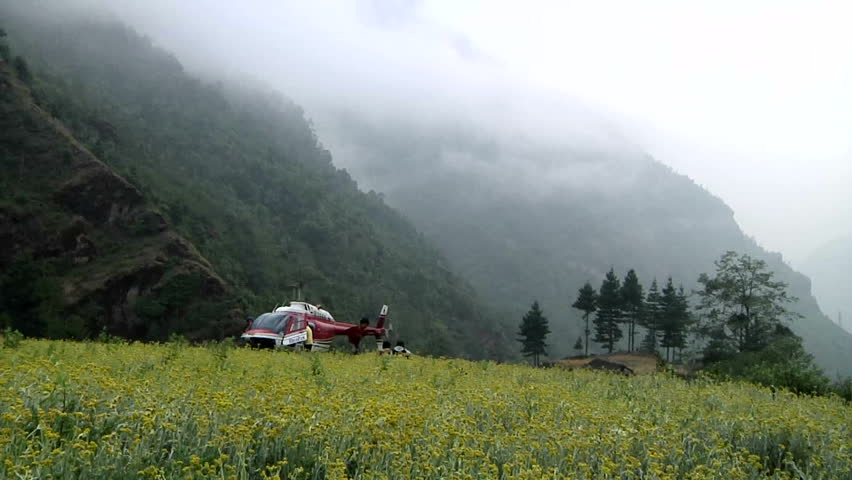 A helicopter waiting in a Sherpa's flower garden on the way to Lukla Airport, near the base of Mt. Everest.