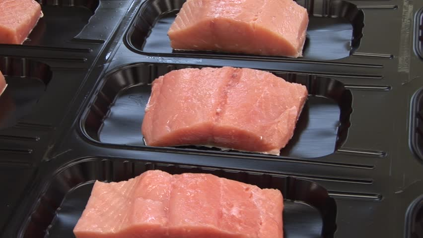 Vacuum packing red fish (trout, salmon, pink salmon). Seafood processing plant