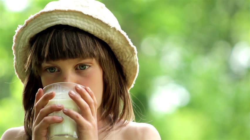 Boy drinking milk.Portrait of a boy drinking milk.The child in a cap drinking milk in nature.