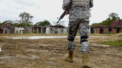 Ungraded shot of Army soldier walking through ruins
