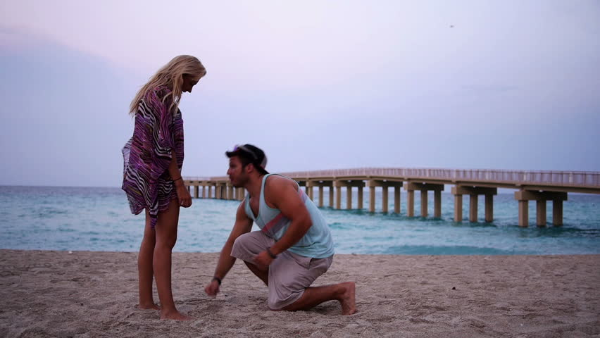 A man proposes on the beach.