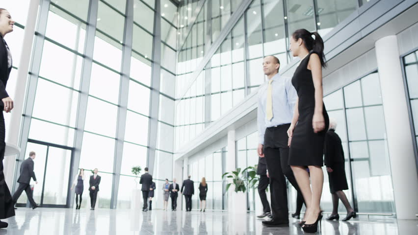 Diverse young team of business people meet and shake hands in a busy modern office building. Other workers can be seen making their way around in the background. In slow motion.