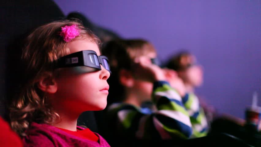 Three kids looking to a 3D movie smiling