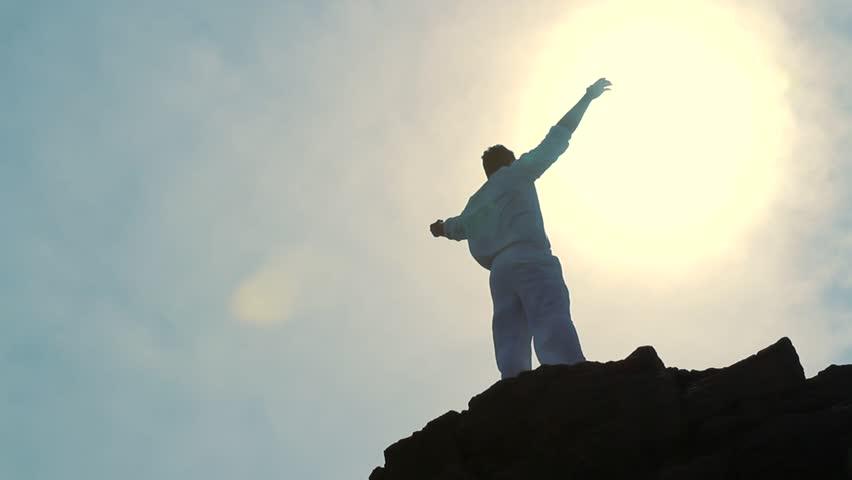 Worship Pose Silhouette of Man on Mountain Peak Raising Religious Arms at Sun