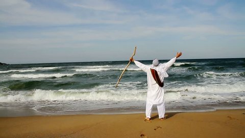 Middle Eastern Man with Staff Walking toward Sea Religious Concept HD