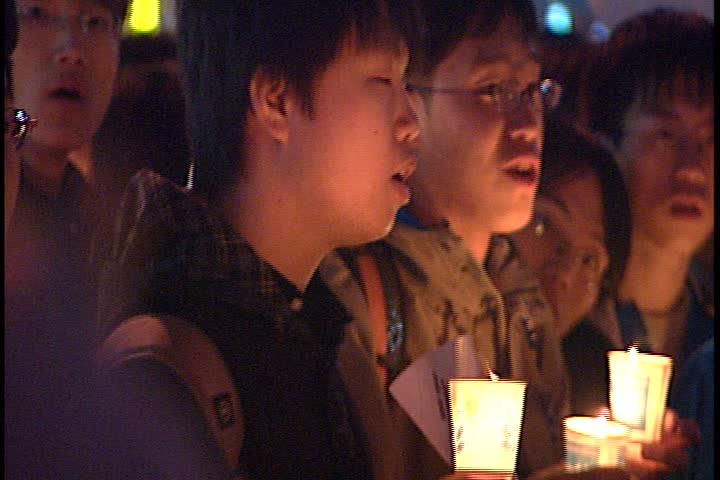SEOUL - MARCH 02, 2003: Night time peaceful anti-war demonstration in Jung-gu; CU young men in crowd holding lit candles.